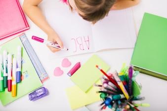 子供がメモ帳に手紙を書く
