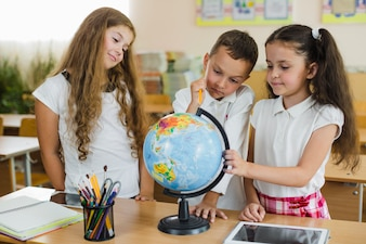 Children looking at globe standing on table