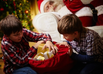 Children looking for their gifts with santa sleeping