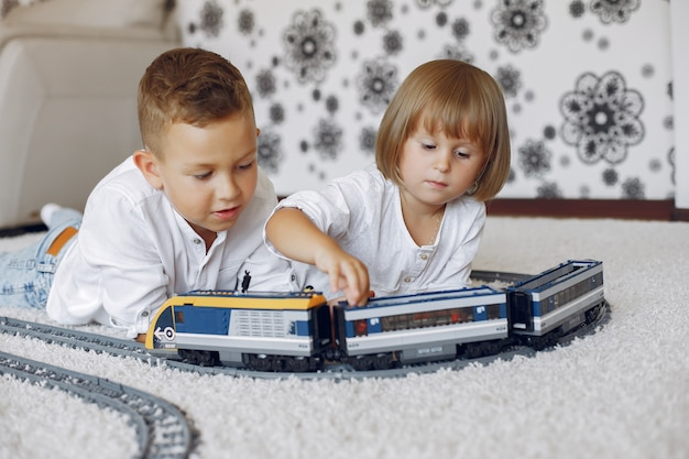 Children playing with lego and toy train in a playing room