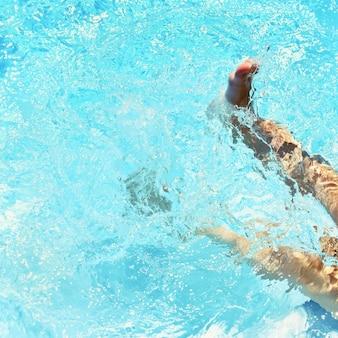 水の中の子供たちの足。夏のプール。美しい透明な青い水と旅行や休暇のための背景。