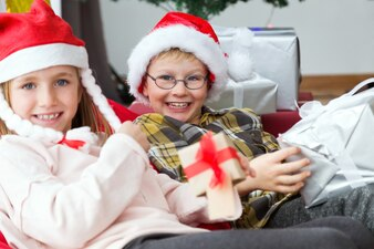 Children smiling with presents and santa hat