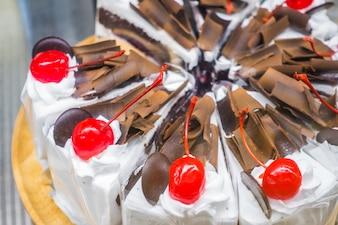 Chocolate cake with red cherries .