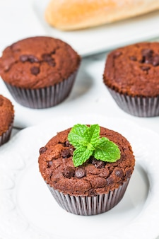 Chocolate muffin with mint on a wooden table