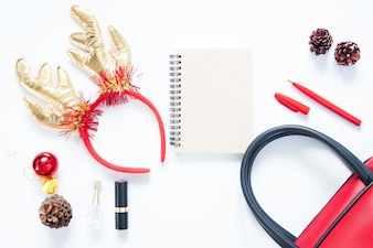 Christmas composition. Christmas fashion for girl, cosmetics, bag, pine cones, notebook and red pen with copy space. Flat lay, top view