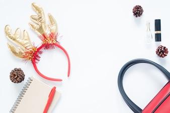 クリスマスの組成。クリスマスファッション、女の子、化粧品、バッグ、松のコーン、ノート、コピースペースと赤いペン。フラットレイ、トップビュー