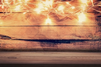 Christmas light on wooden background and wooden table. Christmas table background with space for product.
