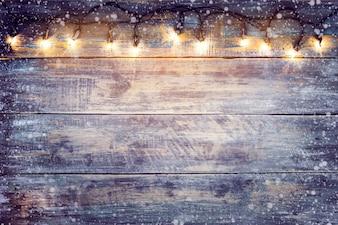 クリスマスライトは、木のテーブルに雪の球。メリークリスマス(クリスマス)背景。トップビュー、ボーダーデザイン - 素朴でヴィンテージスタイル