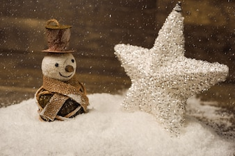 Christmas star and snowman on wooden board with snow