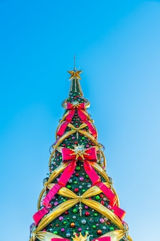 Christmas tree with big bows on a blue background in vertical