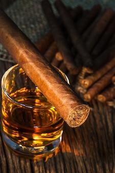 古い木製のテーブルの上にウイスキーのガラスのシガー