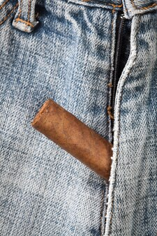 Cigar poke out of the zipper of jeans