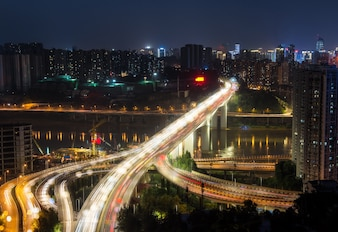 City interchange overpass at night with purple light show in chong qing