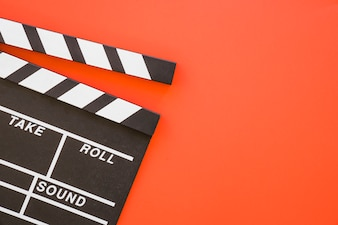Clapperboard on red background with space