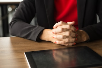 Clasped hands of businesswoman and digital tablet