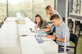 クラスメートは図書館のテーブルで読む