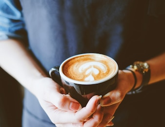 Close up hands of barista woman holding cup of hot cappuccino coffee in the cafe
