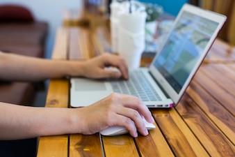 Close-up image of female hand writing on laptot