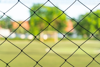 Close-up net with soccer field background