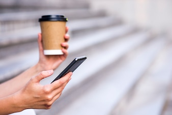Close up of a businesswoman using mobile phone and holding paper cup. Close-up detail of a businesswoman hand holding paper cup and using a smartphone