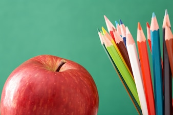 Close-up of a red apple with colorful pencils