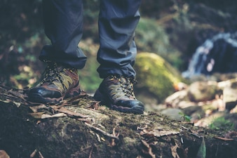 Close up of adventure man feet walk on a mountain path.