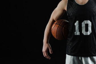 Close-up of basketball player with ball under his arm