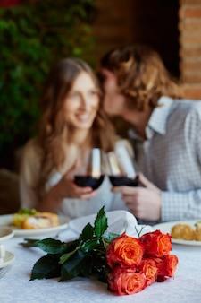 カップルのキスと花束のクローズアップ