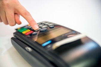 Close-up of cards servicing with POS-terminal, isolated on white background.Female hand with credit card and bank terminal