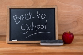 Close-up of chalkboard with blackboard duster and apple