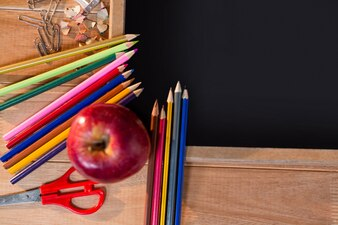 Close-up of chalkboard with colored pencil and apple