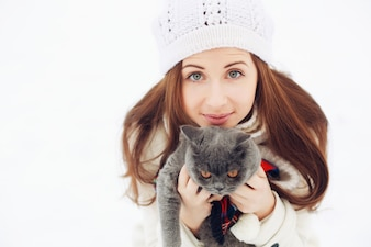 Close-up of charming woman playing with her cat