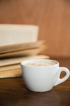 Close-up of coffee cup and book