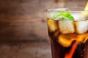Close-up of cola with a straw
