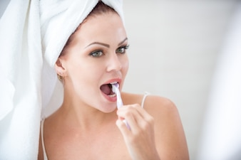 Close-up of concentrated woman brushing teeth