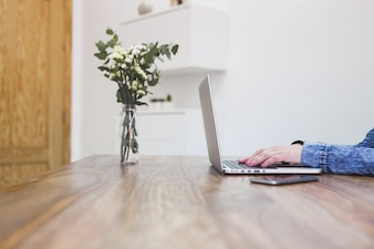 Close-up of desk with businesswoman working and vase