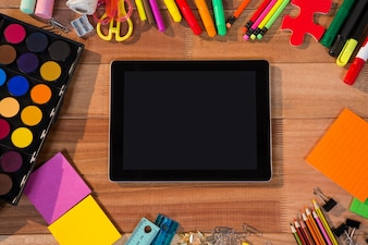 Close-up of digital tablet with various stationery