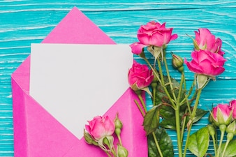 Close-up of envelope with blank note and flowers