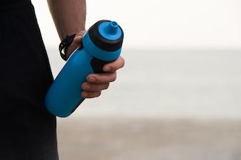 Крупный план бутылочки для фитнес-шейкера в мужской руке