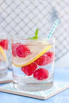 Close-up of fizzy drink with raspberries and slice of lemon