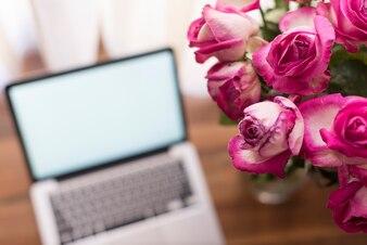 ぼやけたノートパソコンのバックグラウンドを持つ花のクローズアップ