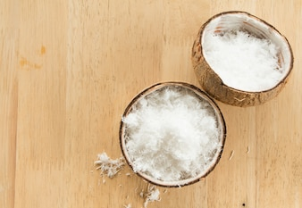 Close up of Freshly grated coconut in shell on wood table.