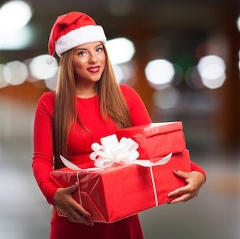 Close-up of girl with santa hat and presents