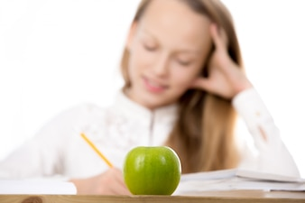 Close-up of green apple on desk