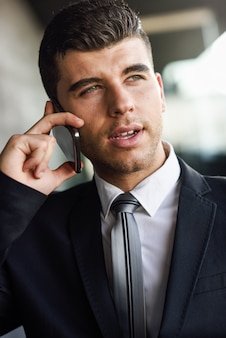 Close-up of handsome employee talking on the cellphone