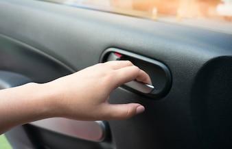 車のドアを開く人間の女性の手を閉じます。
