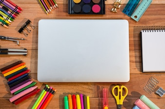 Close-up of laptop with various stationery