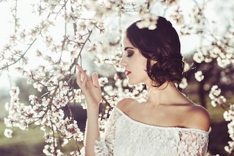Крупным планом прекрасной невесты касаясь ветви на открытом воздухе