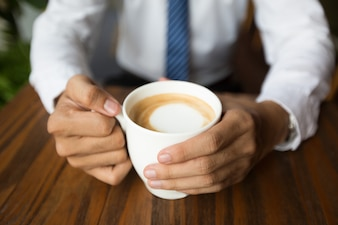 Close-up of male hands holding coffee cup