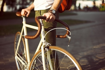 Close-up of man holding his white bicycle